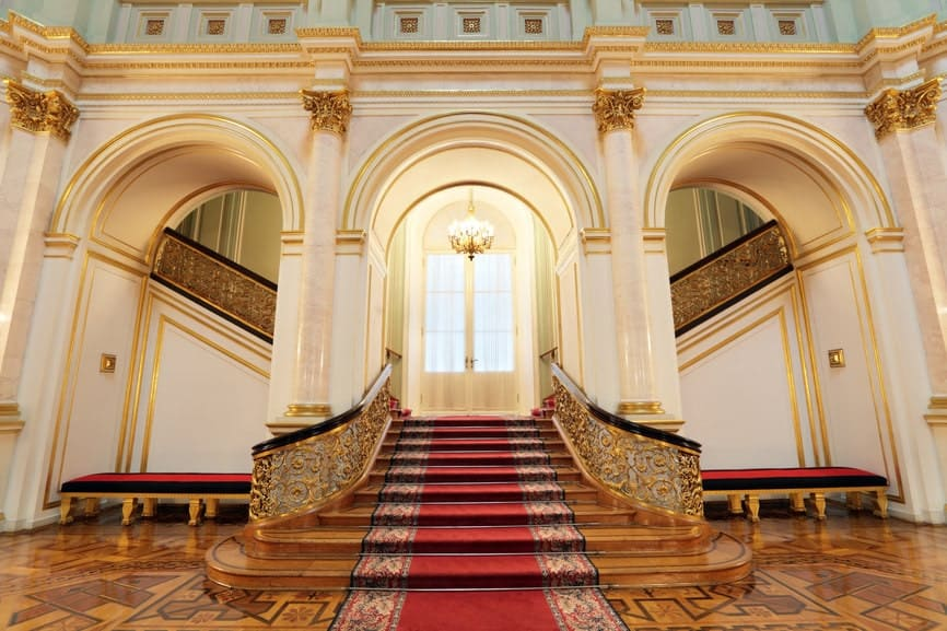Bifurcated staircase fixed on an open archway features gold balustrade lined with dark wood handrails. It includes a classy red carpet that runs along the steps complementing the benches on the sides.