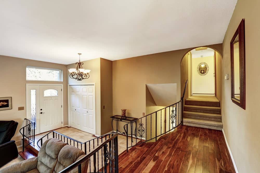 Warm beige foyer with white doors and tiled flooring surrounded with a rich wood bifurcated staircase that features wrought iron railings.