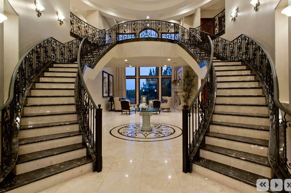 Grand staircase showcases black marble treads against gray risers that match the tiled flooring.