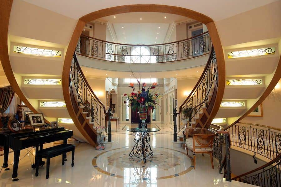 Charming staircase features double wood stringers and illuminating stained glass risers. It has a glass top table at the center with a wooden chair and baby grand piano on the sides.