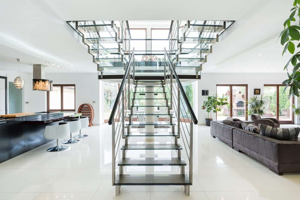 Modern glazed house with an open riser staircase that showcases metal railings and glossy black treads.