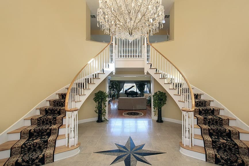 A luxurious crystal chandelier illuminates the two-toned staircase that boasts wooden railings and treads topped with fancy stair runners.