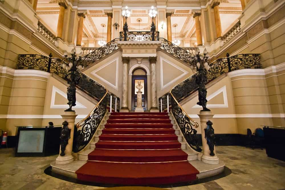 Luxurious staircase boasts a balustrade with intricate design and marble steps topped with a red carpet.