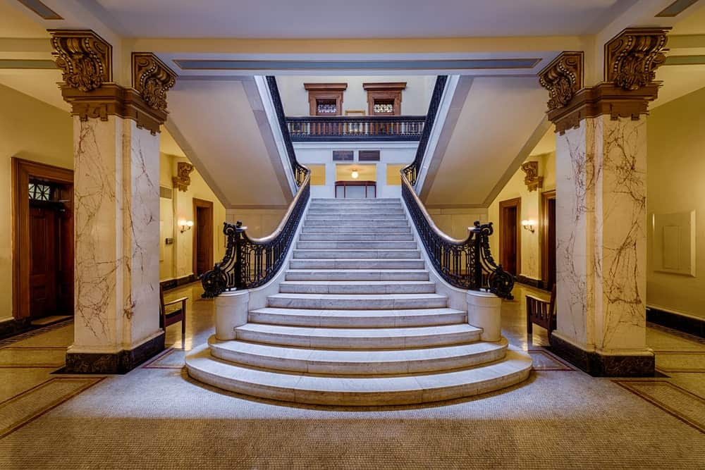 Elegant staircase situated between white marble pillars accented with gold top designs. It has wrought iron railings and concrete steps.