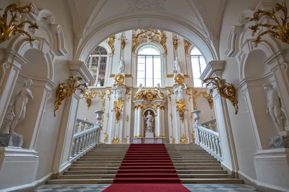 Magnificent concrete staircase on an open archway showcases white balustrade and red stair runner against cream walls accented with gold designs and filled with Greek sculptures.