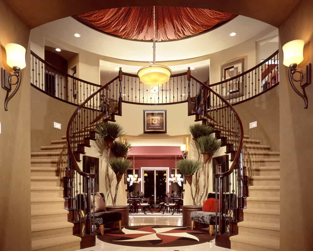 Fabulous home showcases a redwood staircase covered in beige carpet. It is lighted by a chandelier that hung from the round ceiling along with huge sconces.