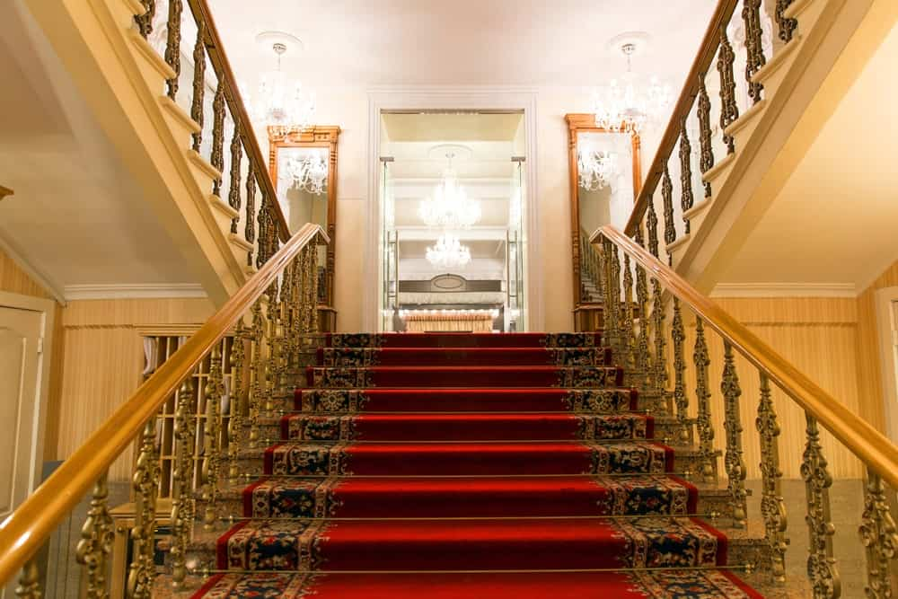 Glamorous staircase offers gold ornate spindles lined with wood handrails. It includes marble steps covered with a red elegant carpet.