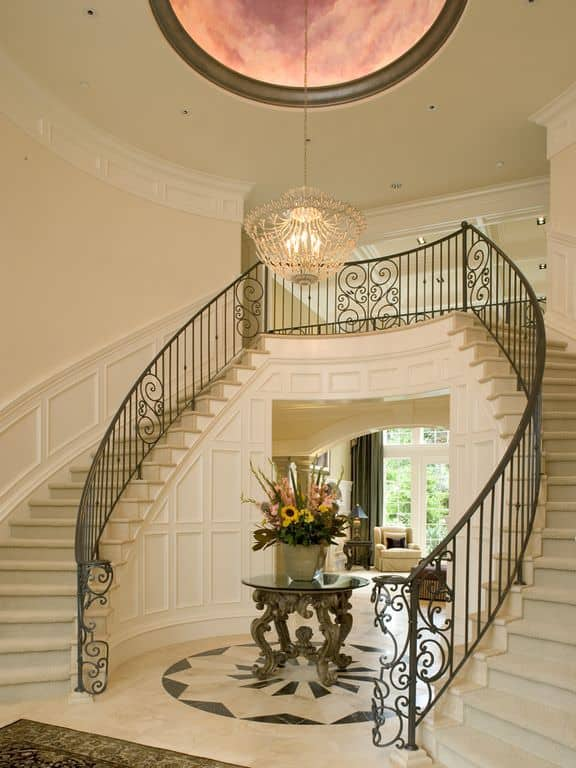 Grand staircase illuminated by a gorgeous chandelier that hung from the tray ceiling. It has white marble steps that complement the flooring covered with gray carpet.