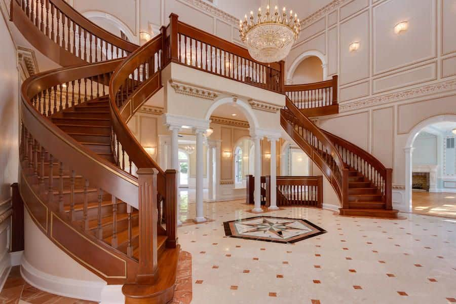 An angled view of a rich wood staircase with gold linings fitted on the blush walls in this grand foyer.