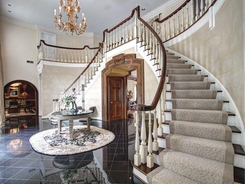 Marvelous staircase in a grand foyer covered in gray patterned carpet and fitted against the stone brick wall. There's a round table in the center sitting on a rug over black marble tiled floor.