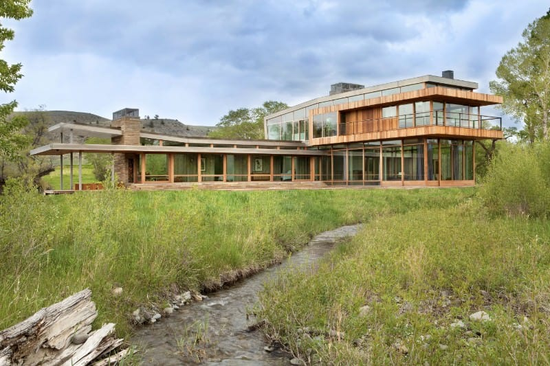 Tall grasses on this narrow river highlight the beauty of this exceptional house.