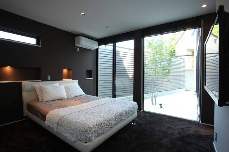 The white traditional bed with white leather headboard is backed against a black wall with small alcoves carved into it that has small pin lights for alight accent. The black carpeted flooring matches this black wall and contrasts the white ceiling that is illuminated by natural light coming in from the glass wall.