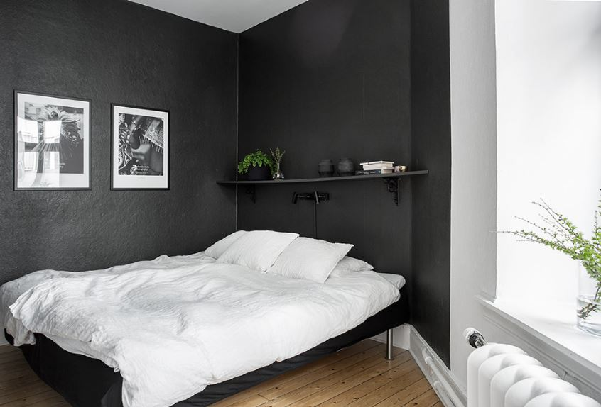 This is a simple and practical master bedroom that has black walls adorned with wall-mounted black and white photos and a single floating shelf above the head of the white cottage bed. There is also a small modern wall-mounted lamp above the head of the bed.