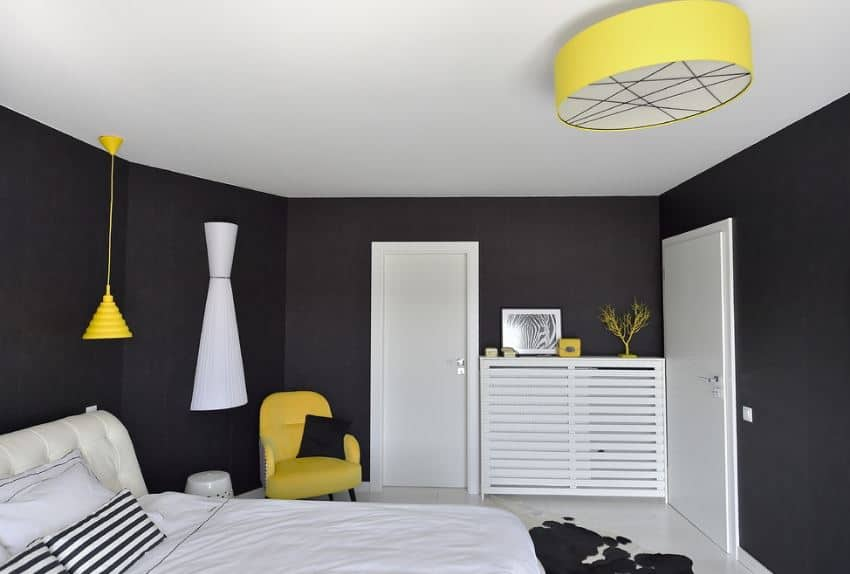 The black walls and white ceiling of this simple bedroom is accented with the yellow elements of the flush-mount lighting, the umbrella pendant light over the head of the bed and the cushioned yellow armchair at the corner that serves as a reading area.