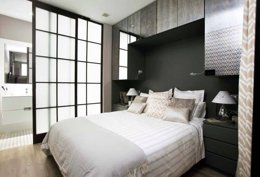 The head of the white traditional bed is inserted into a cozy alcove at the black wall formed by hanging cabinets with a silvery mirror face paired with two black bedside drawers with a pair of table lamps on them. The bedroom is separated from the bathroom area by a pair of tall sliding glass doors with frosted glass.