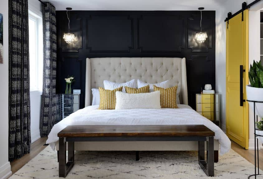 The headboard of the traditional bed is a large charming structure with beige cushions. This contrasts the black wall behind it that has traditional and elegant wooden finishing illuminated by two crystal pendant lights hanging over the pair of modern bedside drawers made of a silver mirror.