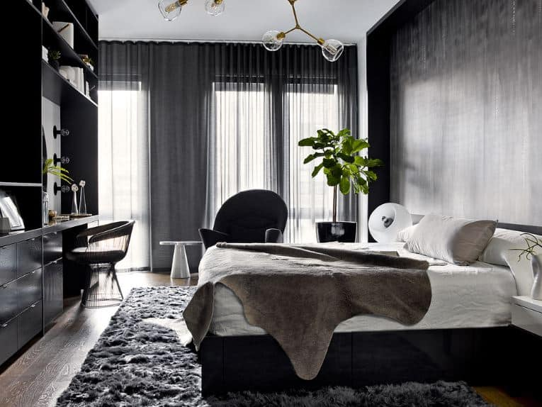 The white cushion of the bed is placed on a black wooden platform that is paired with a black furry area rug beneath it. This is also complemented by a large black wooden structure at the foot of the bed that has built-in shelves, cabinets and a vanity area.