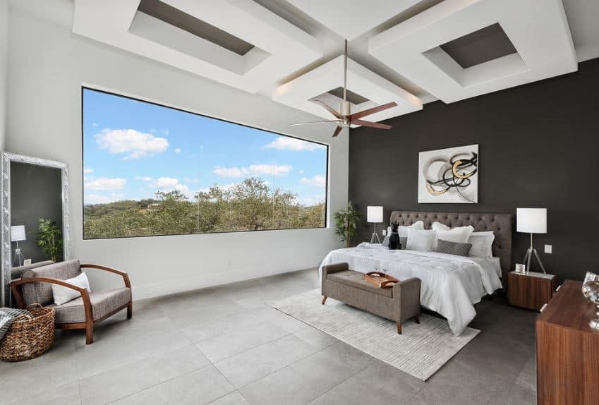 This master bedroom is dominated by large structures like the massive black wall behind the gray cushioned headboard of the traditional bed. Next is the massive glass window at the side of the bed that dominates the white wall. Lastly, the high white ceiling is dominated by trays that are embossed.