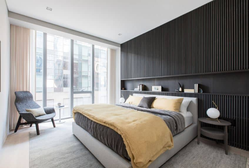 The black wall behind the gray cushioned bed frame has a striped slat-like design. This wall has a long alcove right above the bed that also serves as a shelf for decors and books. The bed is flanked by a couple of modern dark gray bedside tables that stand out against the light area rug.