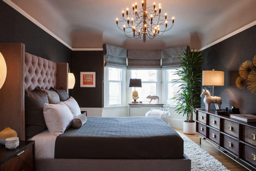 The traditional bed's massive headboard has gray cushions that stand out against the black walls. These black walls are framed with white moldings that separate it from the beige cove ceiling that supports a majestic golden multi-tiered chandelier.