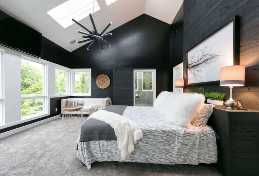The high white arched ceiling is complemented by a skylight window paired with a black modern chandelier that matches the black walls. There is a nice wall-mounted artwork above the head of the white bed with a headboard made of wood painted black.