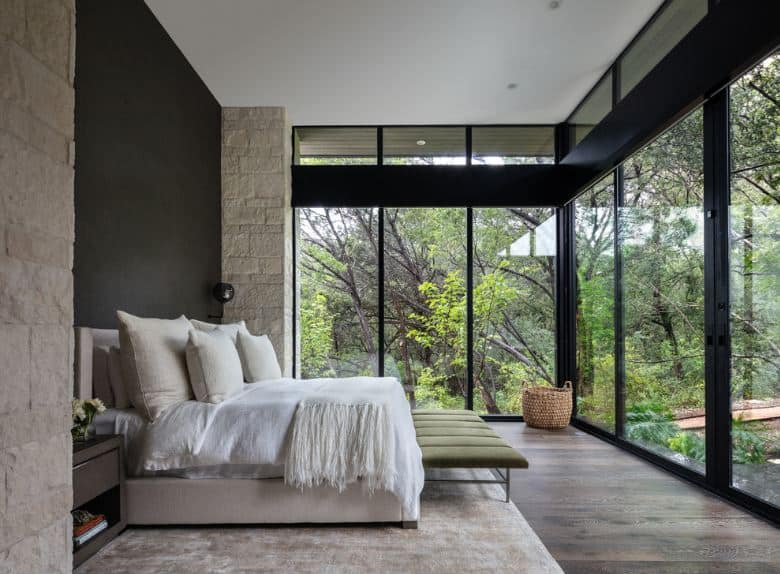 This black-walled master bedroom is airy and bright due to the glass walls that feature a nice view of the surrounding nature. The bedframe is beige that matches the beige area rug over the hardwood flooring. The low cushioned bench at the foot of the bed is green to match the surrounding nature.