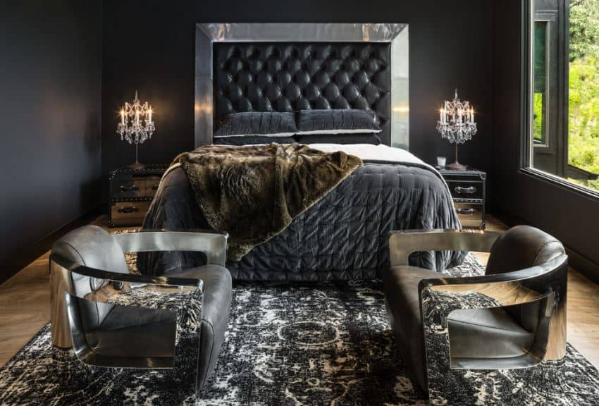 The large black leather cushioned headboard of the traditional bed is framed with stainless metal that shines against the black walls of this master bedroom. There are a couple of modern cushioned armchairs by the foot of the bed over a worn black patterned area rug.