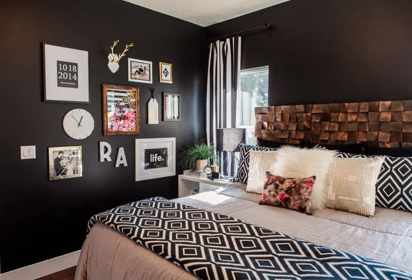 This is a lovely chic master bedroom with a traditional bed that has pink bedsheets and a brass textured headboard that contrasts the black walls. The black wall beside the bed is adorned with a variety of wall-mounted artworks and photos that stand out against the black wall.