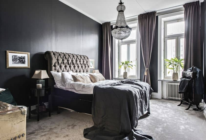 There is a gorgeous hanging crystal pendant light from the middle of the white ceiling that matches the beige carpeted flooring. There are black walls in this master bedroom that is illuminated by a couple of tall windows framed with white molding.