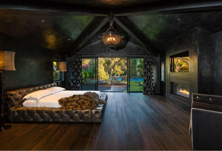 This is a lovely master bedroom that has a black groin arched ceiling with exposed wooden beams also painted black. This is a perfect match for the black walls that has a large black stone structure housing the TV and the modern fireplace at the foot of the brown leather bed.
