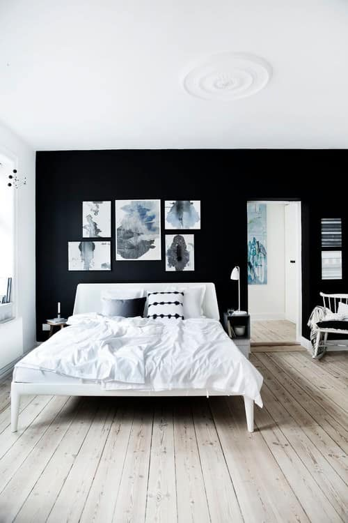 A black and white shabby chic style room, with abstract paintings and a hardwood floor.