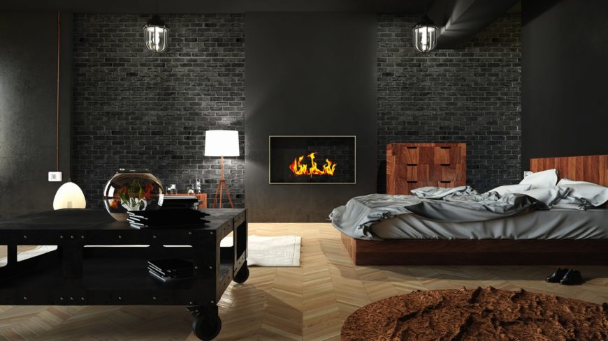 A bedroom with black farmhouse style brick walls, beige hardwood floors, a fireplace, and classic wall-mounted lamps.