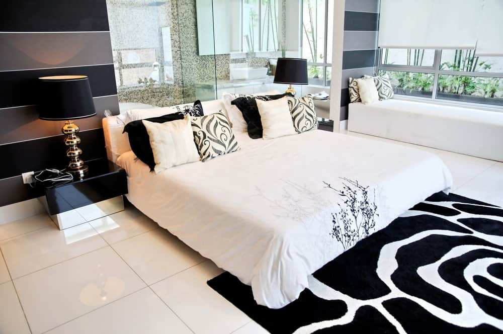 A classy room with a white tiled floor, contrasted with a black and white zebra print rug, a reading nook beside a huge window and a glass-walled bathroom.