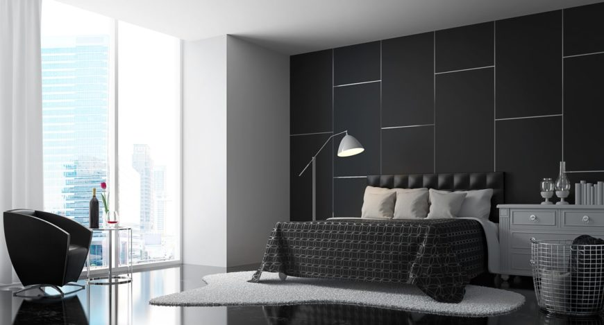 Medium sized room illuminated by a floor to ceiling glass window. An irregular shaped rug gives a bit of contrast to the black floor. It features grayish accents such as the floor lamp, the drawers, and the pillows.