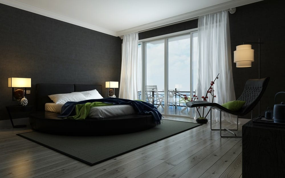 The black walls and dark floors are perfectly balanced by the amount of light coming into the room through the glass-doored porch. Green accents are also incorporated through the pillows and the blanket.