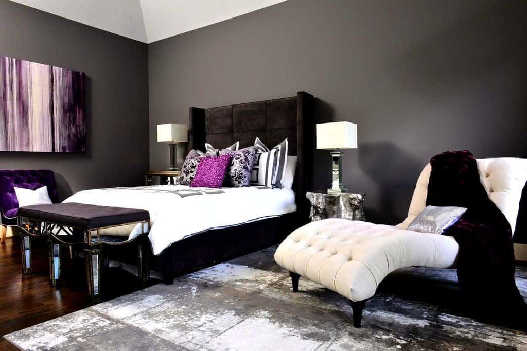 A Victorian-inspired room with exciting purple accents, a bed with a huge headboard, an elegant slanted chair, and a textured rug.