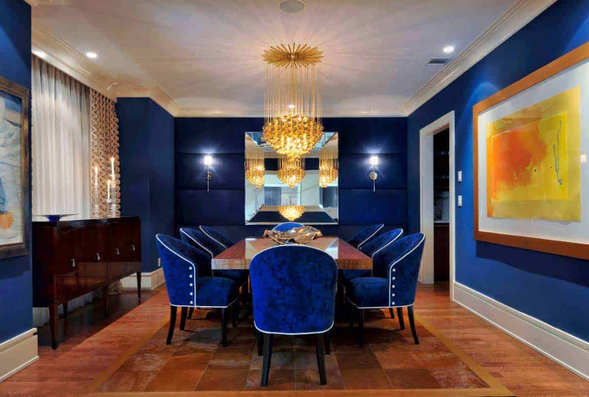 A strikingly blue dining area. Electric blue walls and chairs, a grand golden chandelier, hardwood floors, and a huge abstract painting.