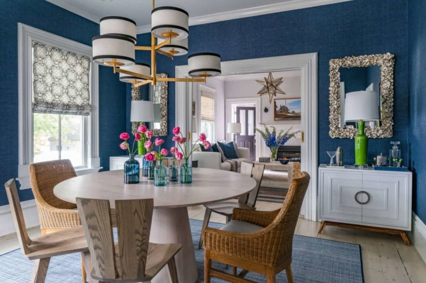 A country style kitchen with blue walls, rustic chairs, and a wooden chandelier.