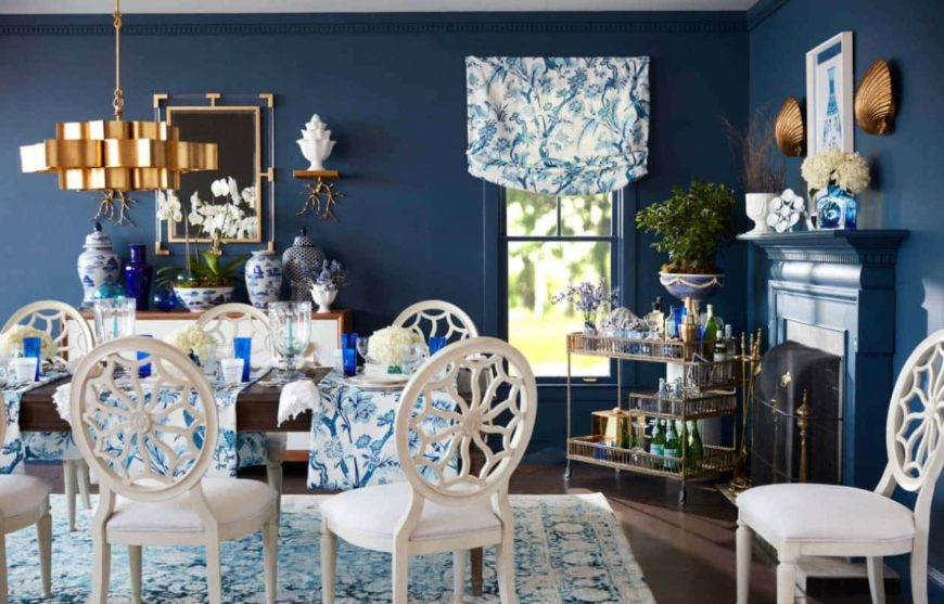A blue country style dining room with floral printed accents, white chairs, a wooden table, a fireplace, and gold accents.