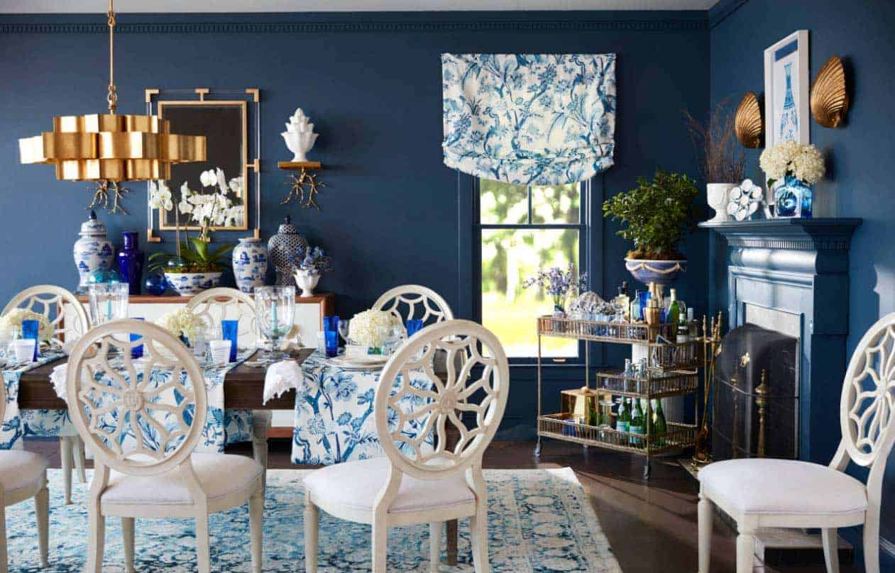 Elegant blue dining room featuring a gold-finished ceiling lighting, white chairs and a blue rug, along with a fireplace.