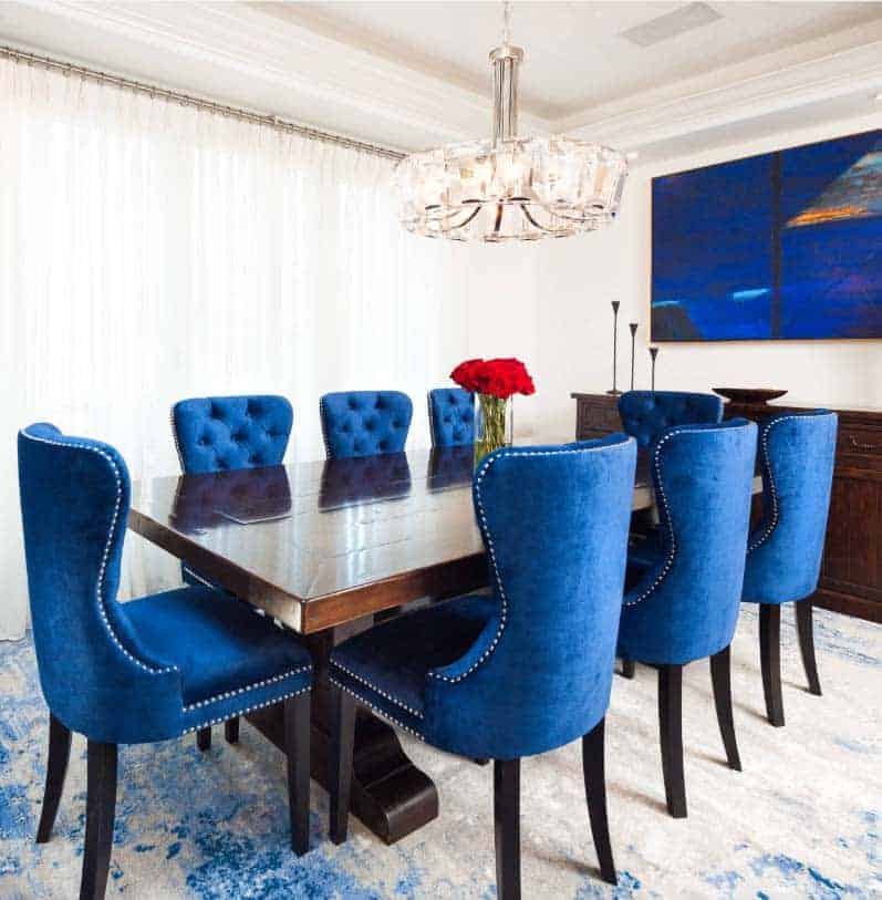 A sleek dining room with eight electric blue chairs, a long rectangular wooden table, white printed rug, and a simple chandelier.