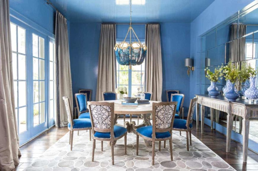 A wide dining room with blue painted walls, huge windows, Victorian-inspired blue chairs, a round wooden table for eight, and a uniquely blue chandelier.