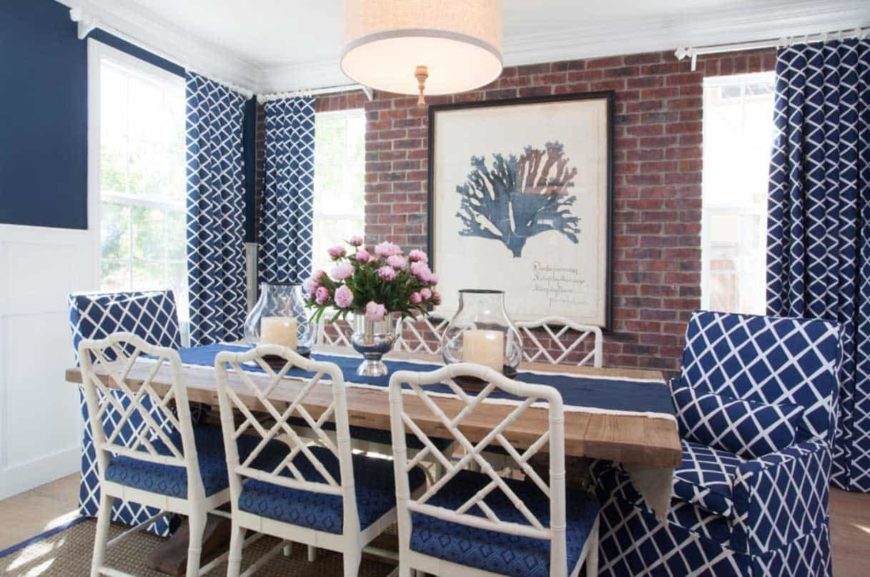 Brick walled dining room with geometric accents and a rectangular wooden table for eight.
