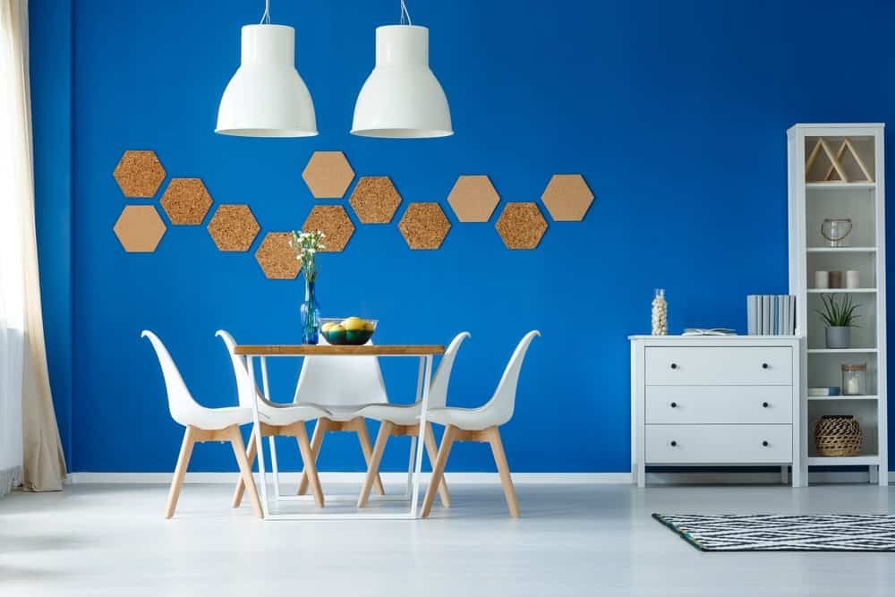 A cleanly designed dining room with a blue painted wall, white chairs, white pendant lights, and octagonal wall accents.