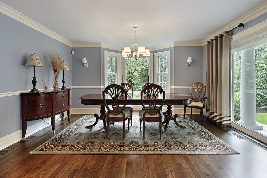 Light bluish walls, huge windows, a traditional style rug, wooden furniture, and a simple chandelier.