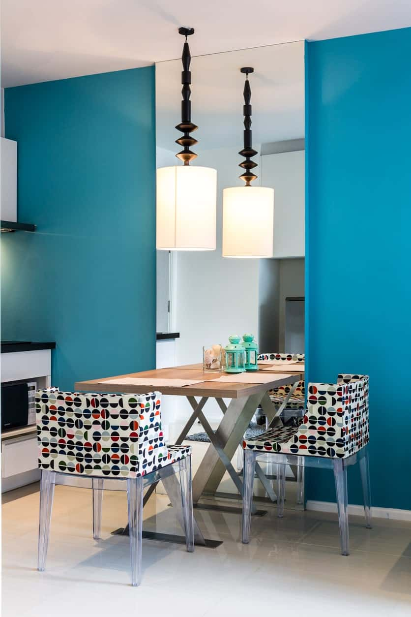 Blue painted walls with playfully printed chairs, a square wooden table for two, a huge floor to ceiling mirror and a pendant light.
