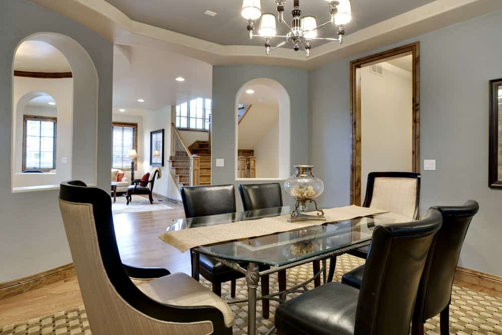 Light grayish blue walls, beige hardwood floor, a glass table for six, black leather chairs, and a chandelier.
