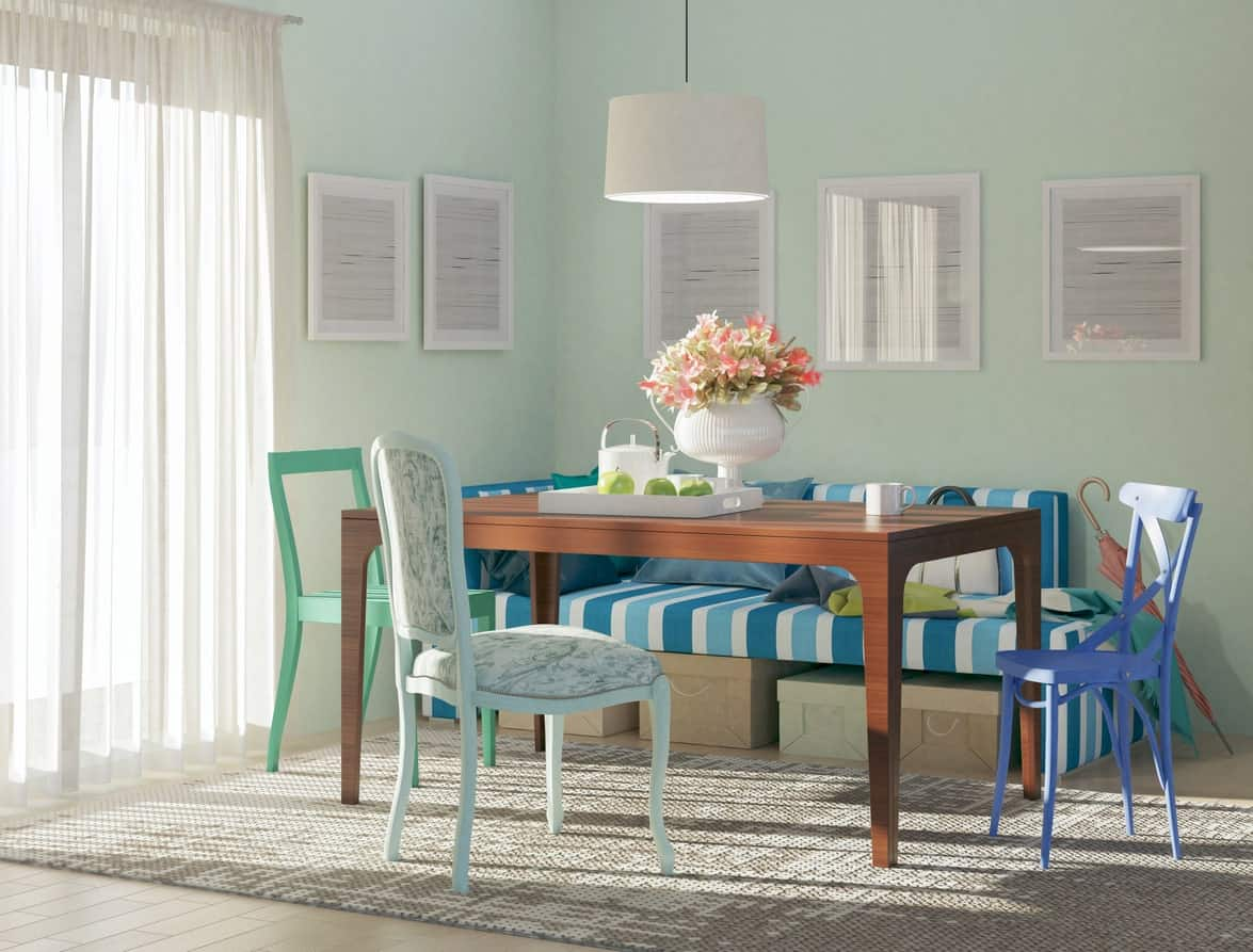 A shabby chic style dining area with blue pastel tones, a mixture of prints, a rustic wooden table, and a simple pendant light.