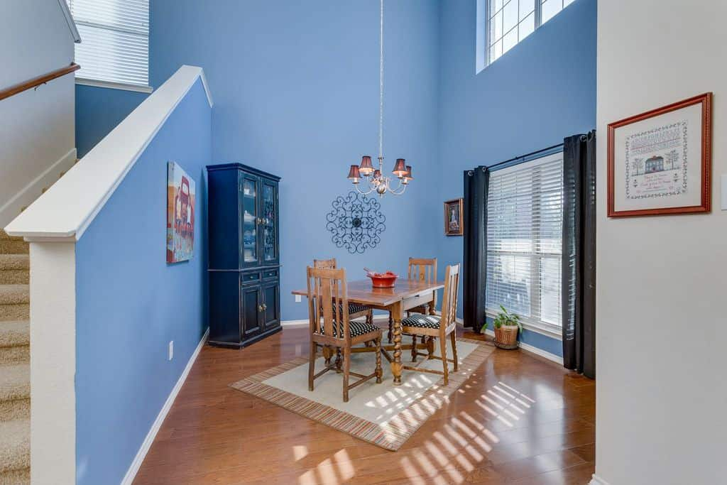 Pastel Blue walls, a huge window, hardwood floors, rustic dining set for four, a traditional cabinet, and a chandelier.