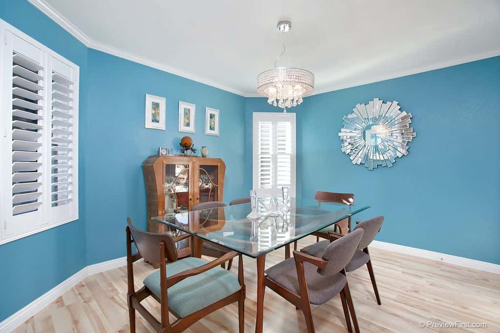 A calming blue dining room with blue and gray chairs, a glass table for six, and a silver chandelier.